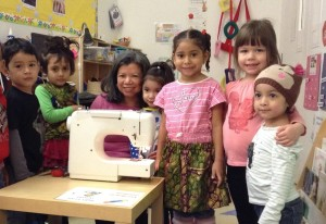 Students and teacher posing with a sewing machine