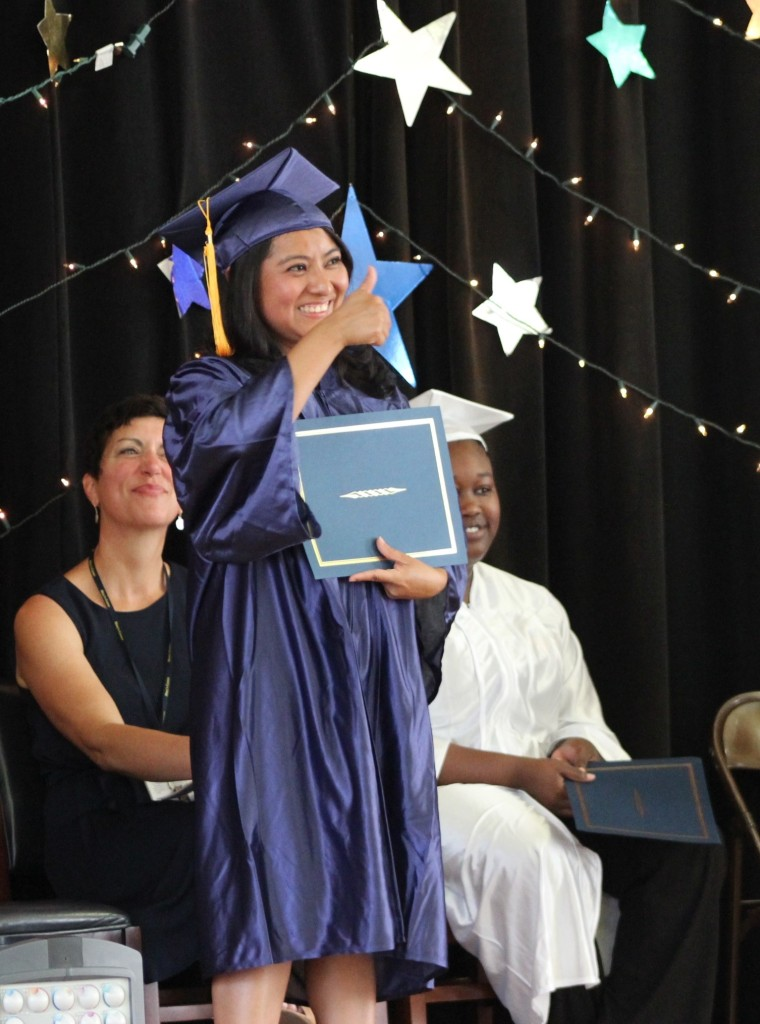 Student giving thumbs up after receivng her diploma